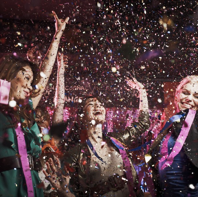Laughing friends under falling confetti --- Image by © Serge Kozak/Corbis